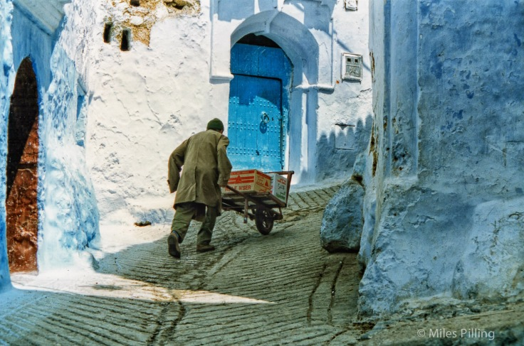 Pushing goods up a hill in Chefchaouen, Morocco