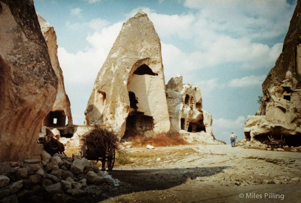 Lone figure walks away in a landscape of cave homes in Cappadocia, Turkey. 1992